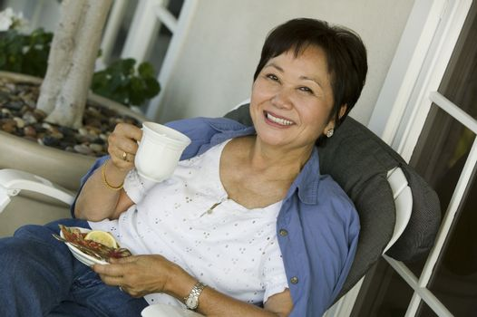 Woman drinking tea on porch (portrait)