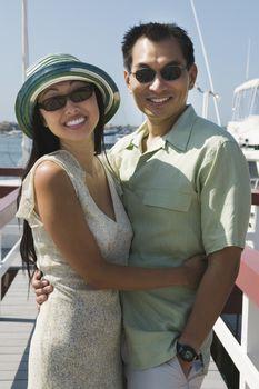 Couple embracing on pier (portrait)