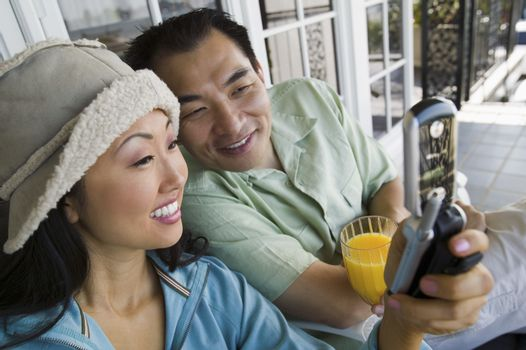 Couple using mobile phone on porch