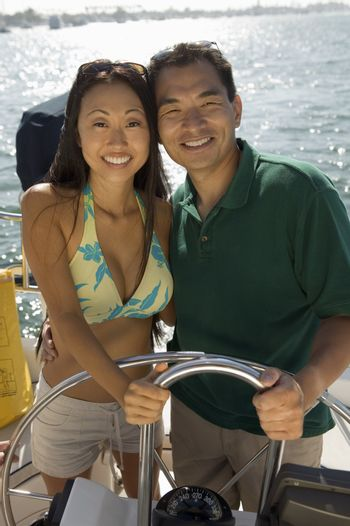 Portrait of a happy Asian couple steering a sailboat