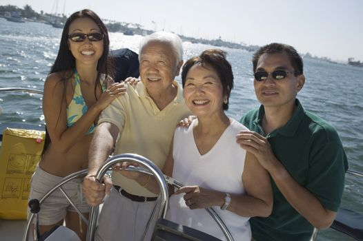Portrait of happy family at steering wheel of sailboat