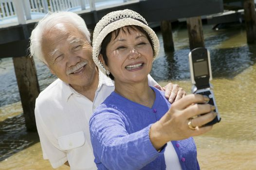 Senior couple photographing themselves by pier