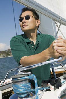Asian man raising sail on the sailboat against clear sky