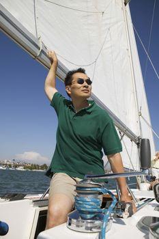 Man looking away while sailing boat