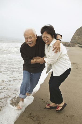 Mature couple playing in surf on beach
