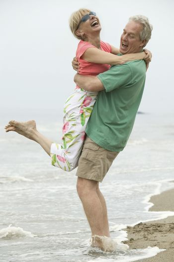 Couple embracing in surf
