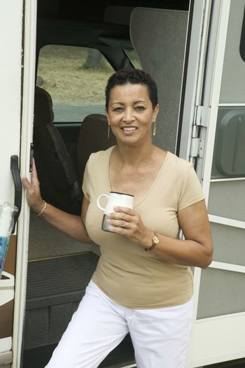 Woman with drink beside motor home (portrait)