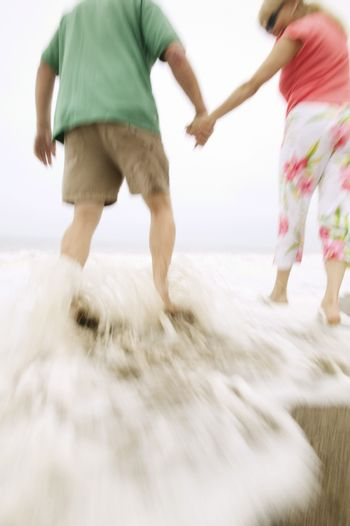 Couple holding hands walking in surf