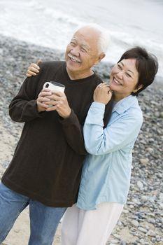 Senior couple at beach looking at camera