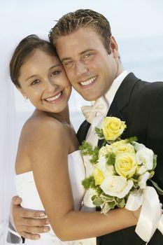 Portrait of loving newlywed couple standing cheek to cheek outdoors