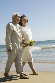 Senior newly weds walking arm in arm on beach