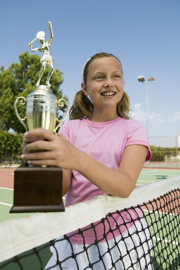 Girl at Tennis Net Holding Trophy