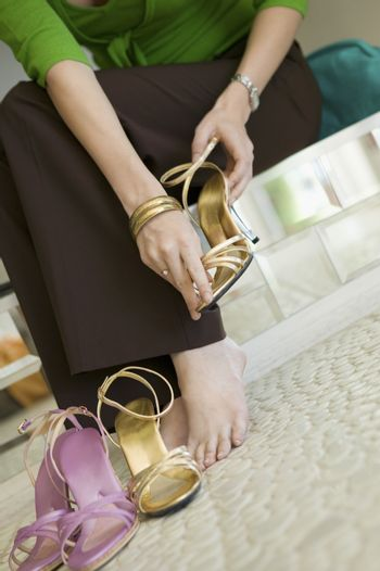 Woman Trying on Shoes in clothing store low section ground view