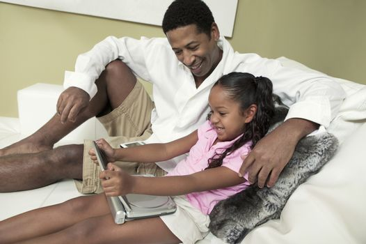 Father and Daughter on sofa Watching Movie on Portable DVD Player