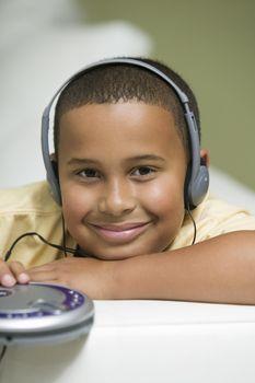 Boy on sofa Listening to portable CD player portrait