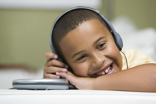 Closeup of a happy relaxed boy listening to portable CD player on sofa