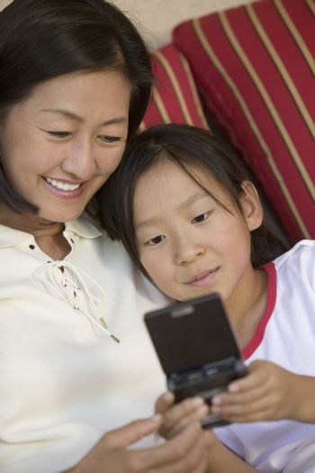 Mother and Daughter Playing Handheld Video Game on sofa