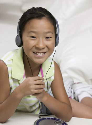 Young Girl on sofa Listening to portable CD player