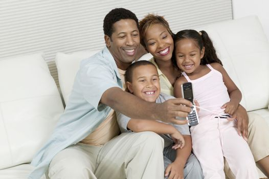 Family Taking Picture of family on sofa with Camera Phone
