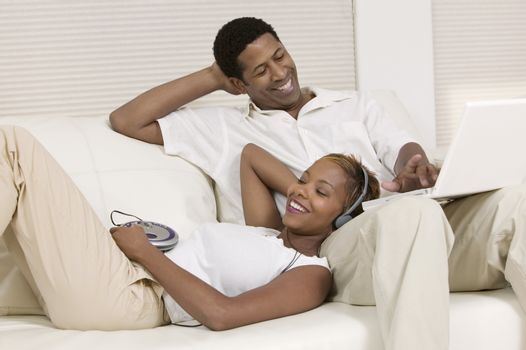 Couple Relaxing on Couch with portable CD player and Laptop