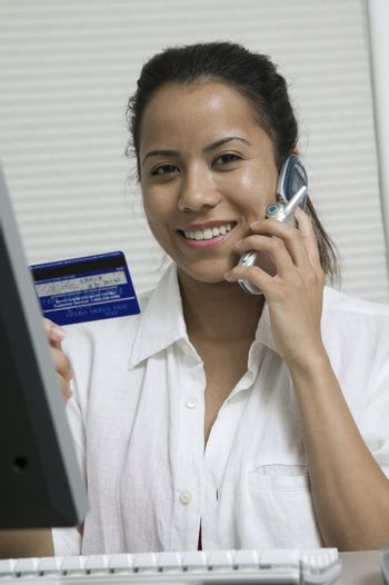 Woman making credit card purchase on cell phone portrait