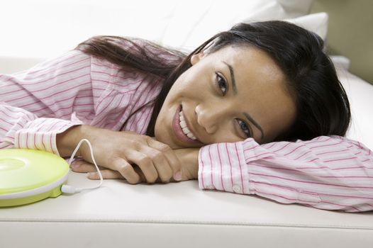 Woman Lying on sofa by Portable CD Player portrait