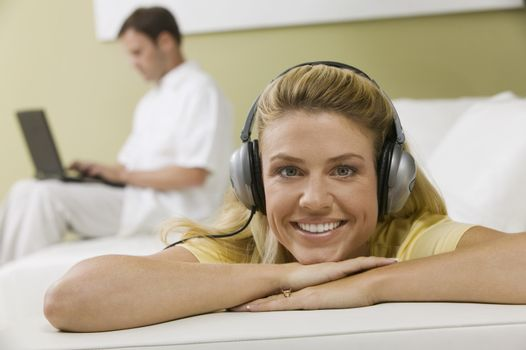 Woman Listening to Music While Husband Works