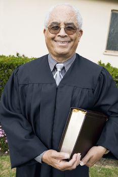 Senior Preacher in garden with Bible portrait