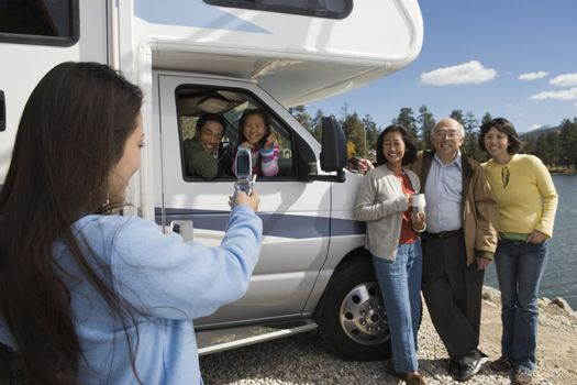 Teenage daughter photographing family with cell phone outside RV at lake