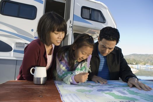 Two parents and daughter looking at map on picnic table outside RV
