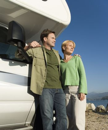 Couple standing by RV