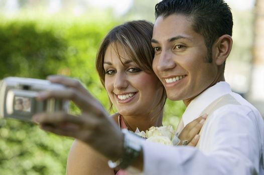 Well-dressed teenage couple taking photograph outside