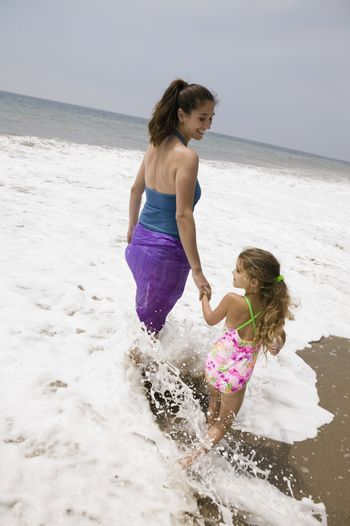 Mother and daughter walking through surf