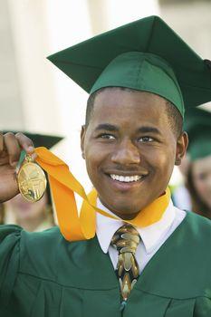 Graduate Holding Medal outside