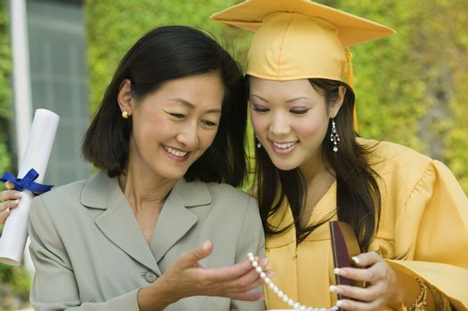 Graduate and mother admiring necklace gift outside