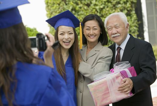 Graduate videotaping other graduate with mother and grandfather outside