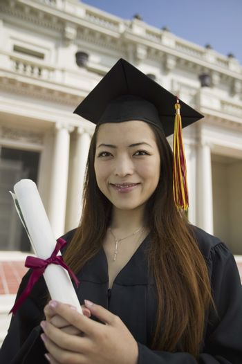 Graduate holding diploma outside university portrait