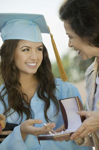 Graduate Receiving necklace from Grandmother outside