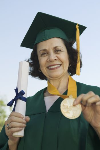 Portrait of a senior woman in graduation attire holding degree and medal