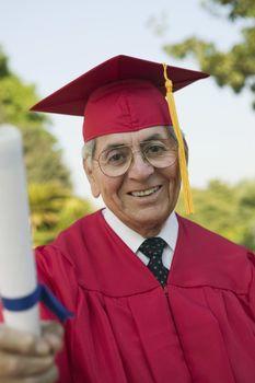 Portrait of an elderly man in graduation attire holding degree