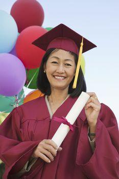 Portrait of a happy mature woman in graduation attire holding degree