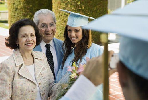 Graduate and grandparents having photograph taken outside