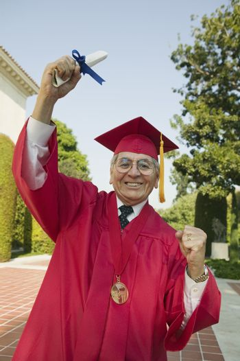Portrait of an excited senior man in graduation attire holding degree