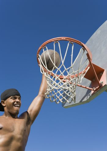 Young shirtless African American making a dunkshot in basket