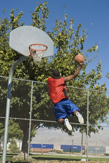 Rear view of African American man jumping to score basket