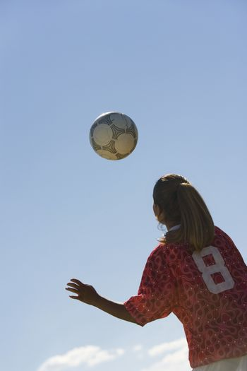 Low angle view of young woman heading football against sky