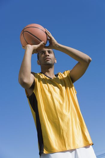 Basketball player about to throw ball against blue sky