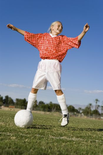 Full length of a young female player playing soccer on field