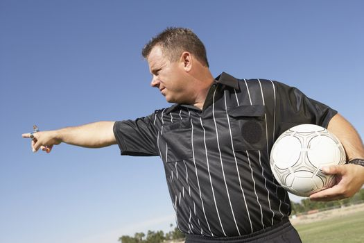 Mature male referee with soccer ball pointing at distance
