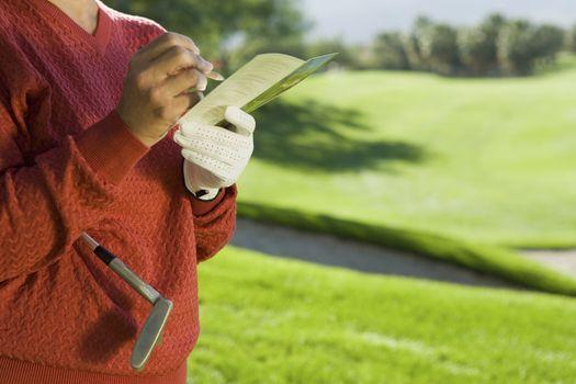 Midsection of a senior woman writing golf score on scorecard